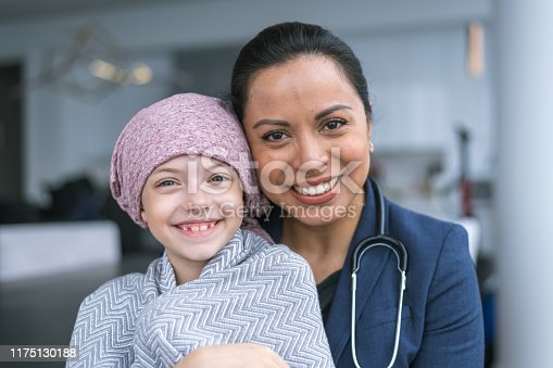 istock Kind doctor comforts young girl with cancer 1175130188