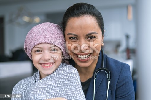 istock Kind doctor comforts young girl with cancer 1175130192