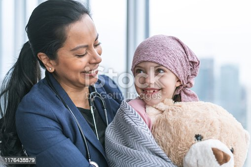 istock Kind doctor comforts young girl with cancer 1176438879