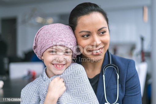 istock Kind doctor comforts young girl with cancer 1176438886