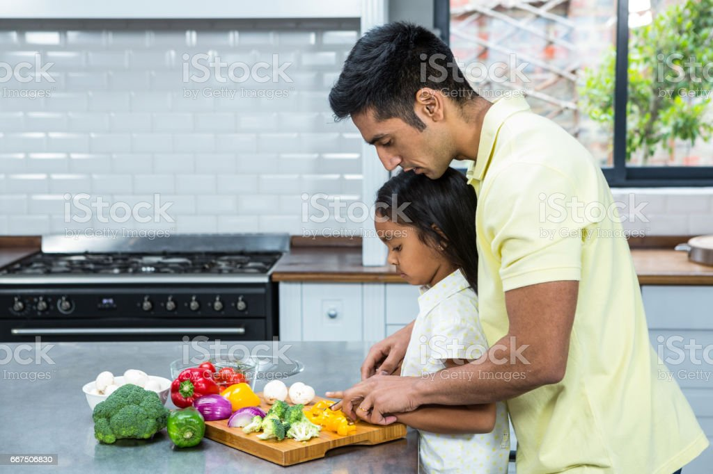 Kind father helping his daughter slicing vegetables foto stock royalty-free