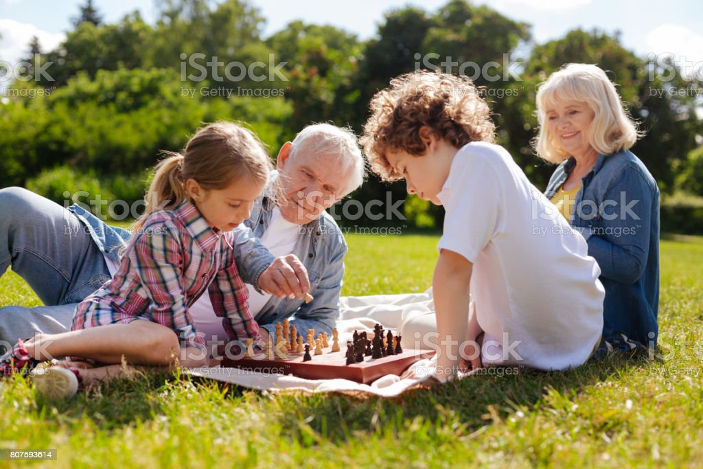 Kind grandpa helping his granddaughter play chess stock photo