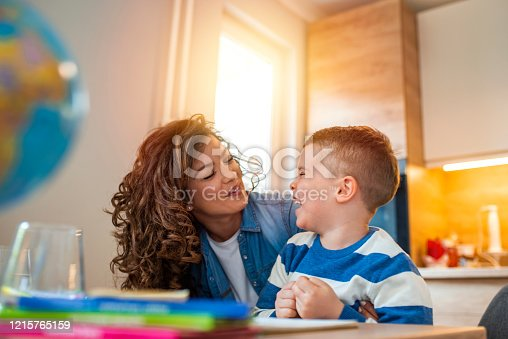 istock Kind mother helping her son doing homework in kitchen. 1215765159