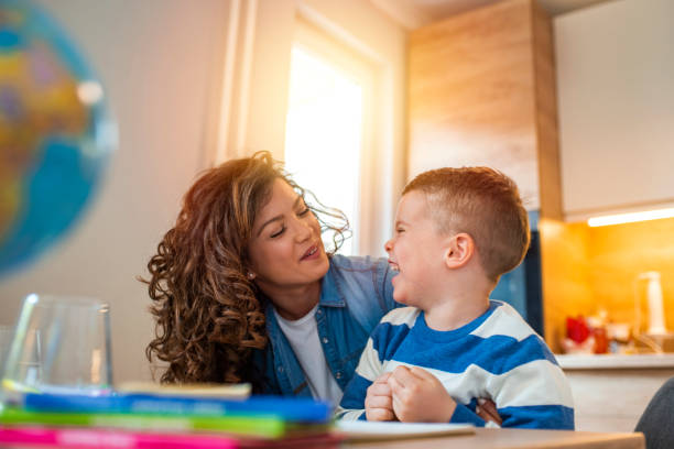 Kind mother helping her son doing homework in kitchen. Kind mother helping her son doing homework in kitchen. Mother Helping Son With Homework At Table. Children's creativity. Portrait of smiling mother helping son with homework in kitchen at home autism stock pictures, royalty-free photos & images