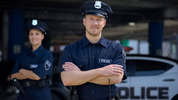 uprzejmi policjanci uśmiechnięci stojący w pobliżu posterunku policji, gotowi do pomocy, - policja zdjęcia i obrazy z banku zdjęć