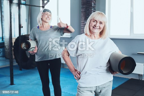 936573360 istock photo Kind smiling lady holding mat while taking group exercise class 936573146