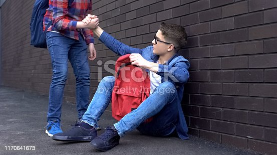 istock Kind teenage student giving helping hand to bullied nerd boy, supportive friend 1170641673