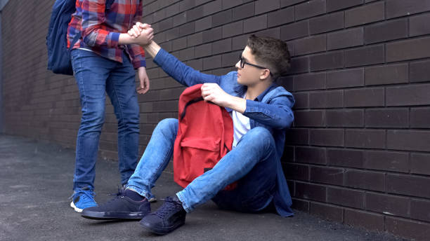Kind teenage student giving helping hand to bullied nerd boy, supportive friend stock photo