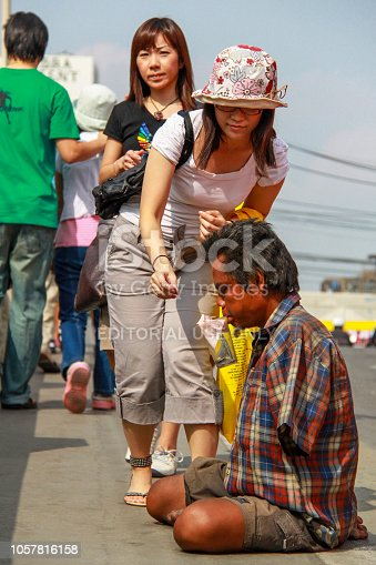 istock Bangkok - 2010: A kind woman giving some money to a destitute on the street. 1057816158