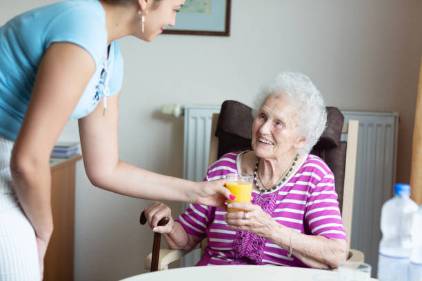 kind young caregiver helping senior woman stock photo