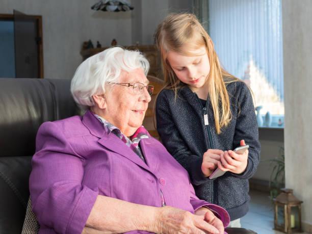 freundlichen weitergeleitet seiner großmutter etwas sind auf dem smartphone - lila mädchen zimmer stock-fotos und bilder