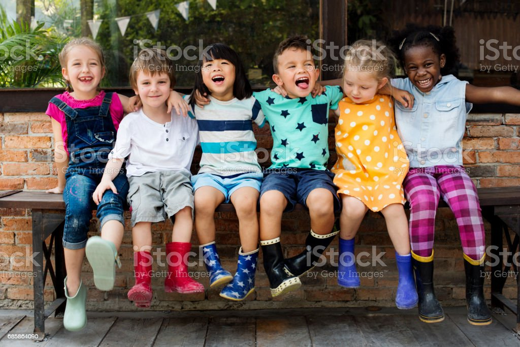 Kindergarten kids friends arm around sitting smiling - Foto de stock de Abraçar royalty-free