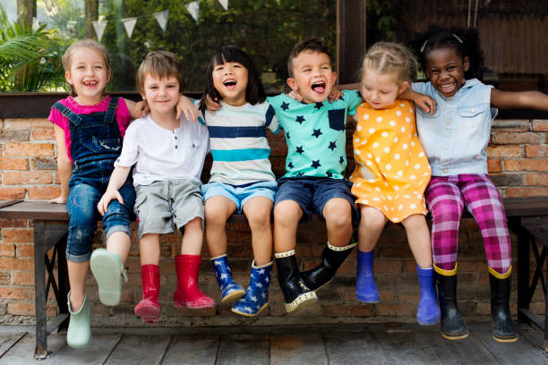 kindergarten kids friends arm around sitting smiling - kind stockfoto's en -beelden