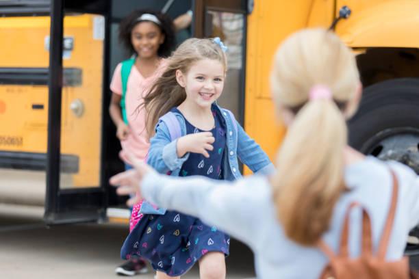 alumna de kinder corre a su mamá después de la escuela - autobuses escolares fotografías e imágenes de stock