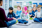 A group of students sits cross legged with their hands on their legs and their eyes closed. In the forefront is a muslim girl who is wearing a hijab.