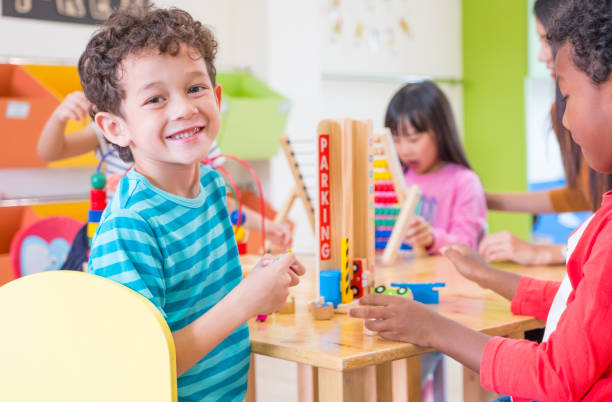 Kindergarten students smile when playing toy in playroom at preschool international,education concept stock photo