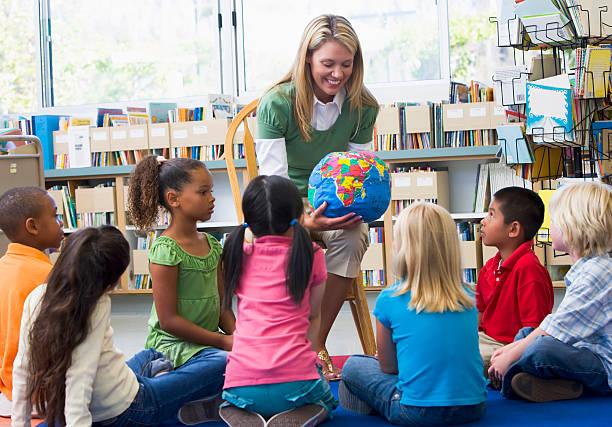 bereits im kindergarten lehrer und kinder, die auf der ganzen welt - erzieherin stock-fotos und bilder
