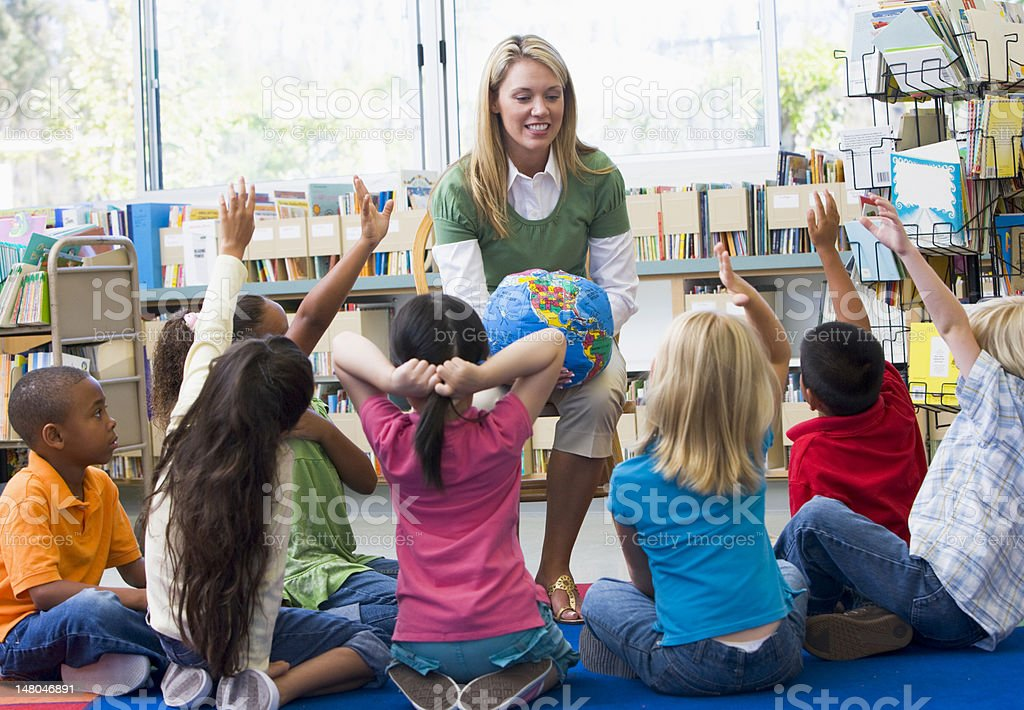 Kindergarten teacher and children with hands raised in library stock photo