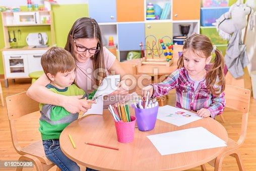 639271192istockphoto kindergarten teacher and kids on creative activities 619250936