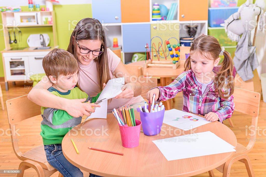 kindergarten teacher and kids on creative activities stock photo