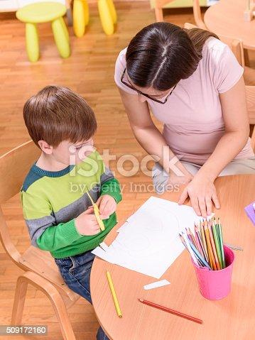 639271192istockphoto Kindergarten Teacher Helping Cute Boy 509172160