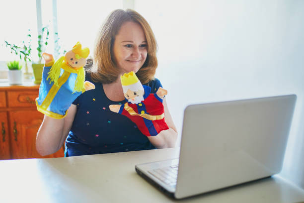 Kindergarten teacher in front of laptop having video conference chat with children stock photo