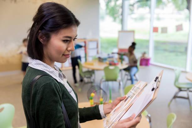Kindergarten teacher prepares class assignment stock photo