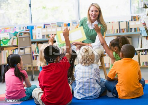 istock Kindergarten teacher reading to children 121350642