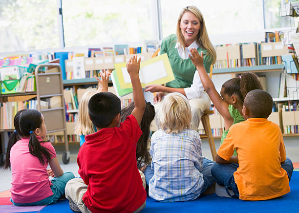 Kindergarten teacher reading to children Kindergarten teacher reading to children in library elementary age stock pictures, royalty-free photos & images