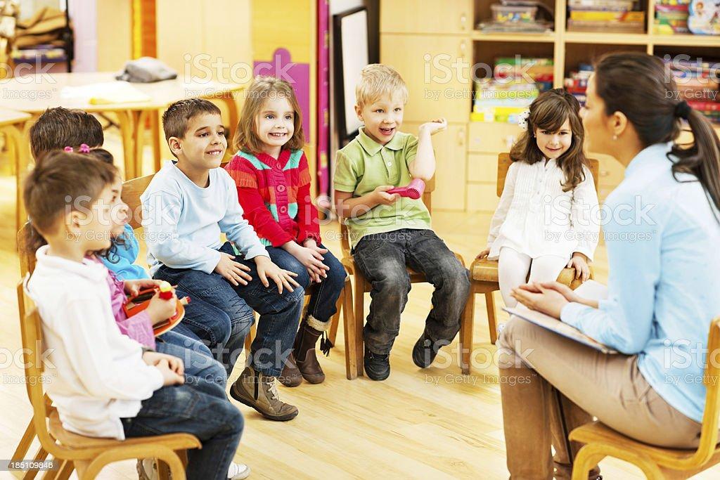 Kindergarten teacher reading to children. stock photo