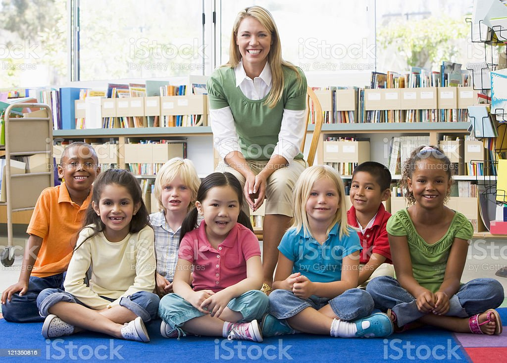Kindergarten teacher sitting with children in library royalty-free stock photo