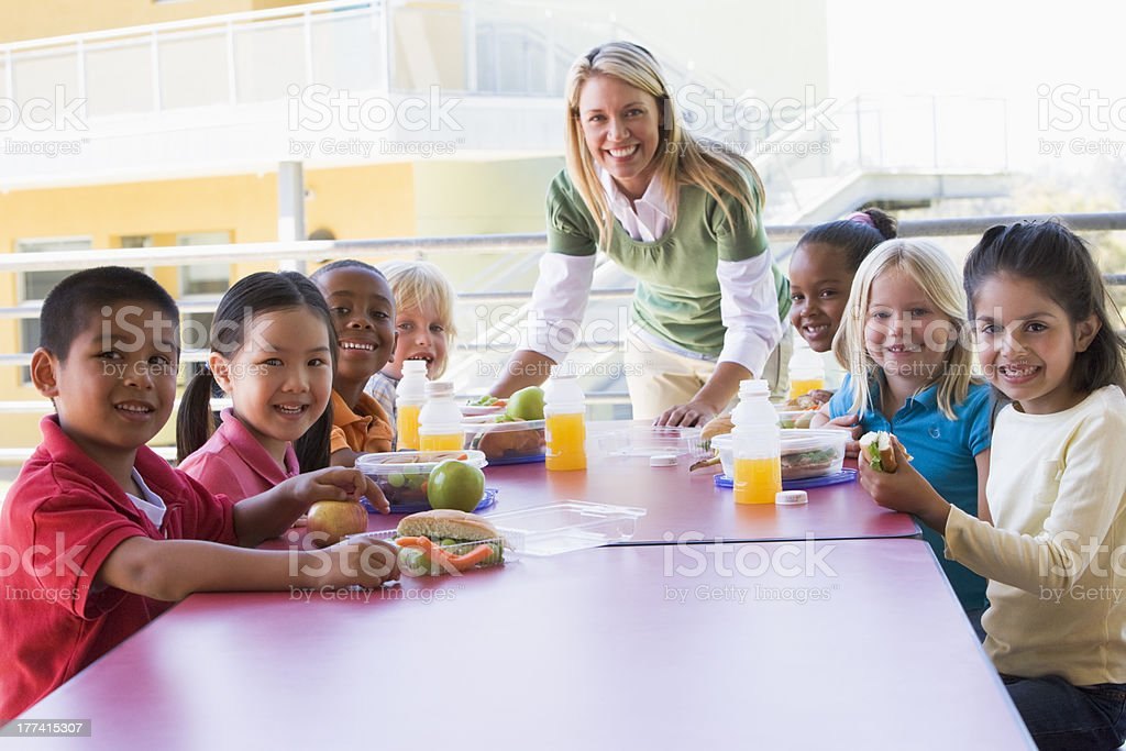 Kindergarten teacher supervising children eating lunch stock photo