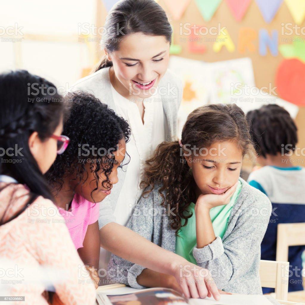 Caring young female kindergarten teacher shows schoolgirls something...