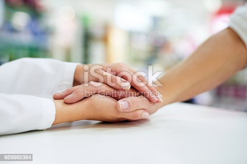 Cropped shot of a pharmacist  compassionately holding a customer's hand