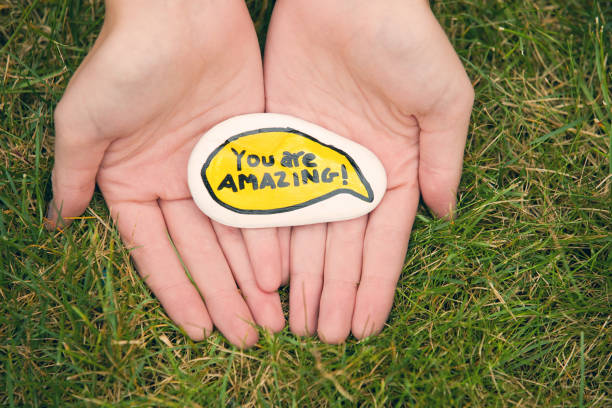 Kindness Rocks You Are Amazing Two hands cupping a kindness rock found in the grass that is painted with the words
