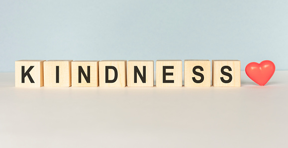 Kindness Word Written In Wooden Cube on a light background
