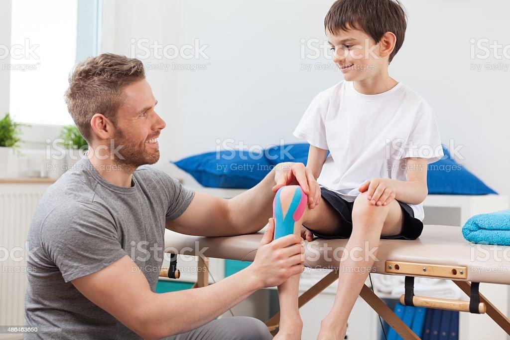 Kinesio taping after knee injury stock photo
