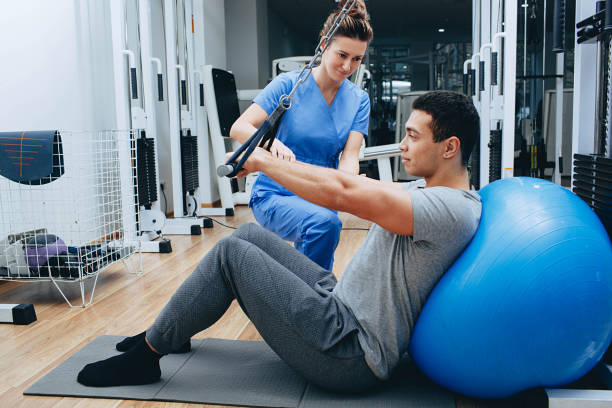kinesiologist helps a mixed race man doing exercises to strengthen his back muscles. treatment of back pain using kinesitherapy. kinesiologist helps a mixed race man doing exercises to strengthen his back muscles. treatment of back pain using kinesitherapy. sports medicine stock pictures, royalty-free photos & images