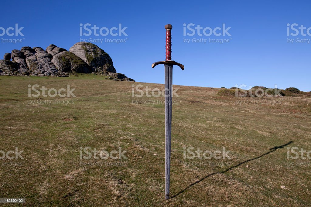 King Arthur sytle sword stuck into ground with rocky landscape. stock photo