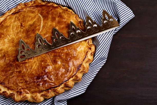 gâteau du roi ou galette des rois en français. tarte traditionnelle d'épiphanie avec la couronne de papier d'or - galette des rois photos et images de collection
