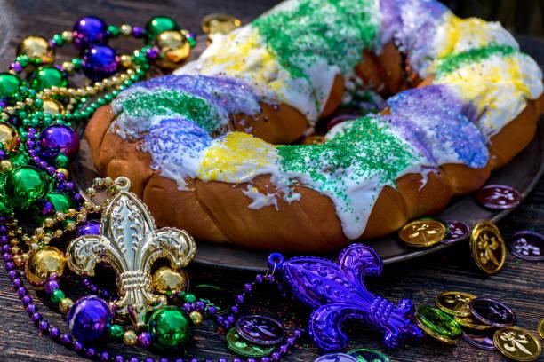 le roi gâteau entouré de décorations de mardi gras - galette des rois photos et images de collection