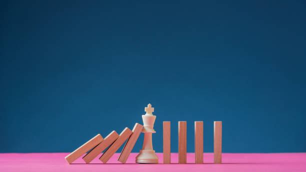 King chess figure standing in the middle of falling dominos stock photo
