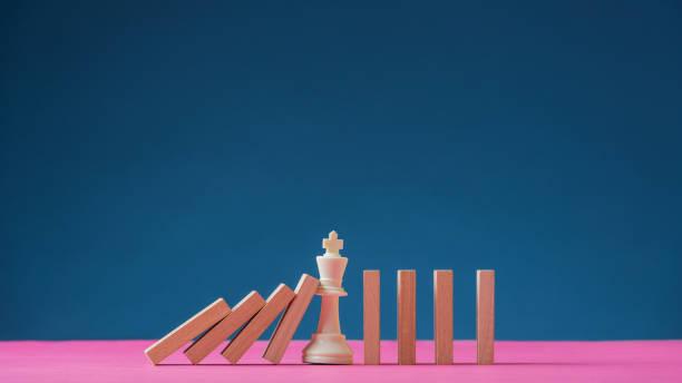 König Schachfigur steht in der Mitte der fallenden Dominos – Foto