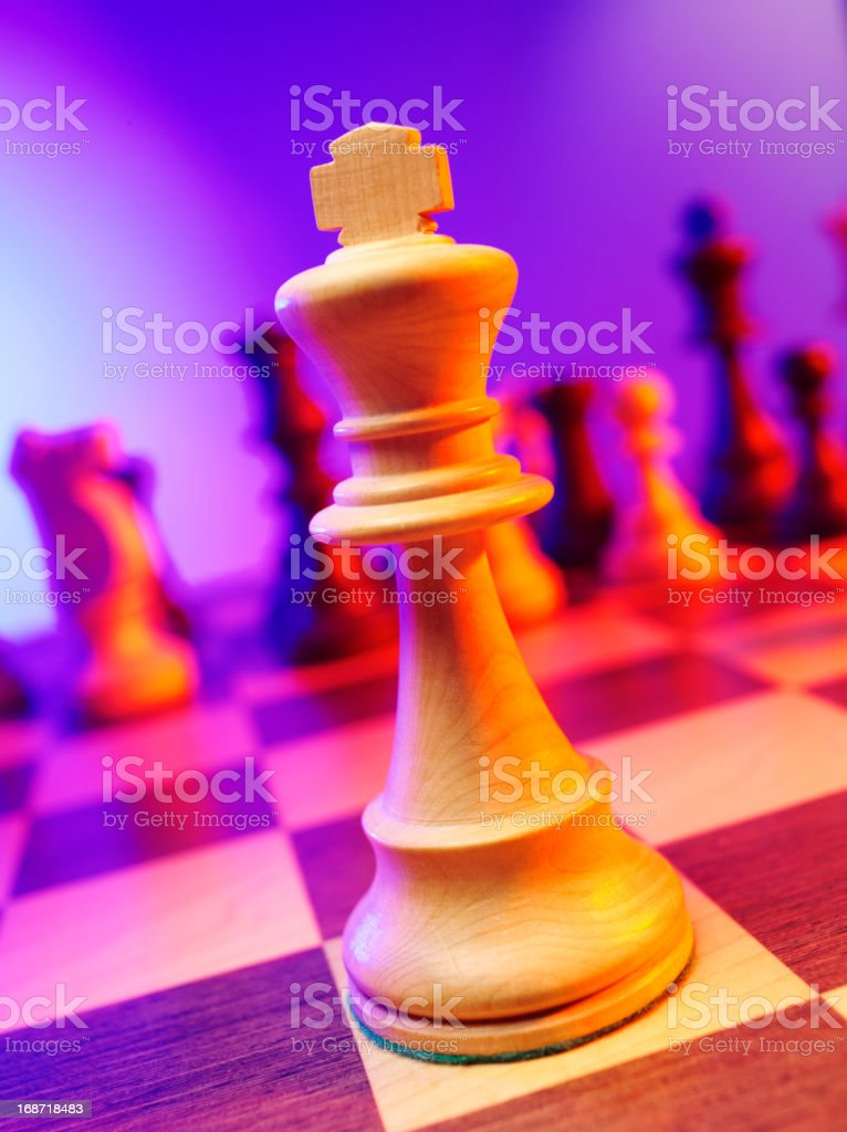 Focus on a single chess king on a board with coloured lighting,...