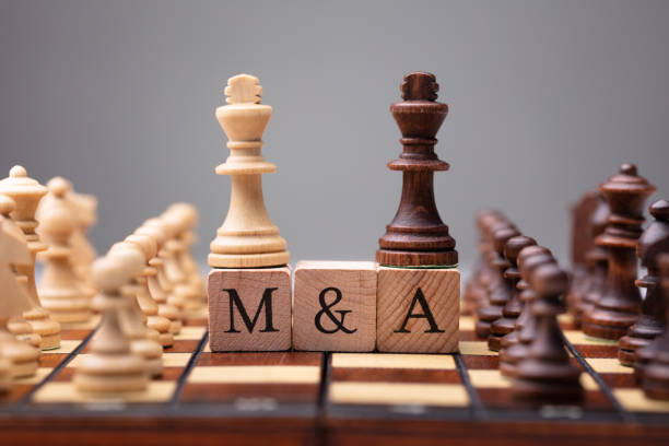 King Chess Pieces With Mergers And Acquisitions Text stock photo