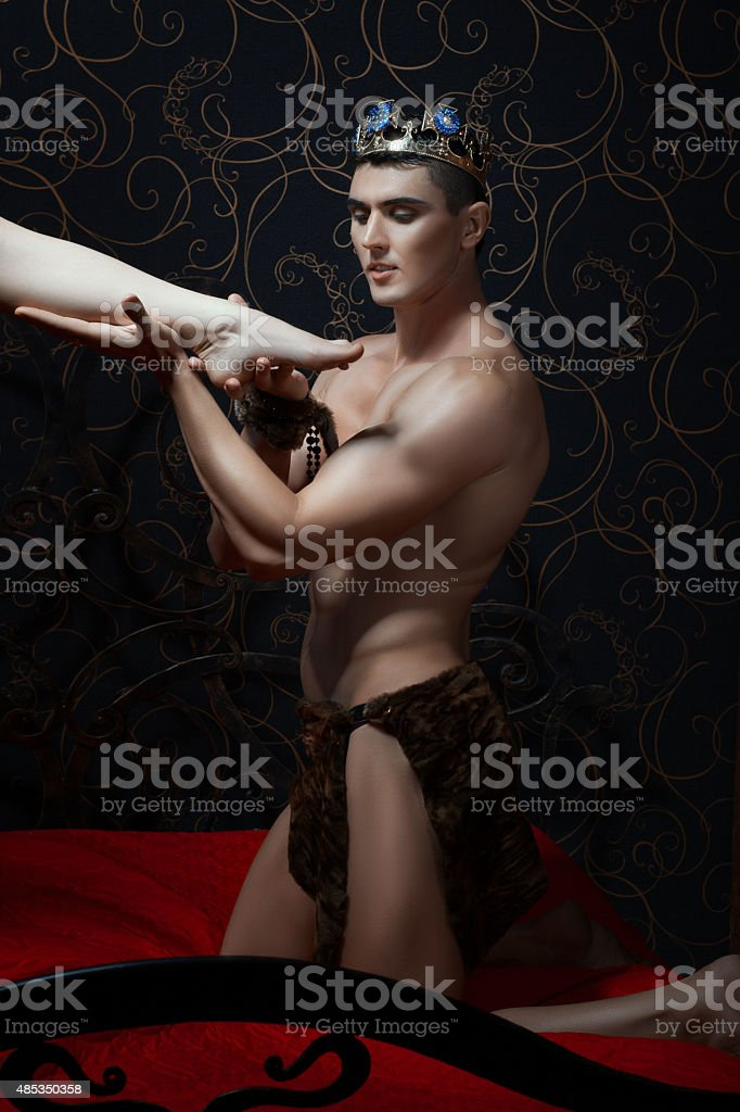 King holds a female leg in hand. stock photo