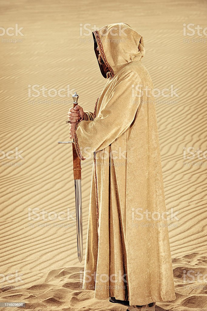 King In Hooded Robe Holding His Sword - Sand Background stock photo