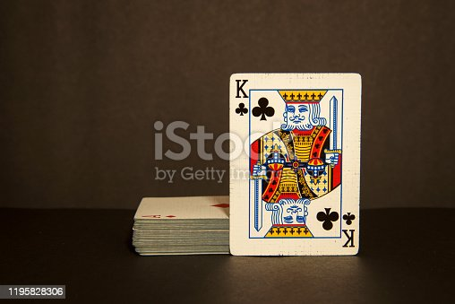 deck of cards with a king of clubs propped against the deck