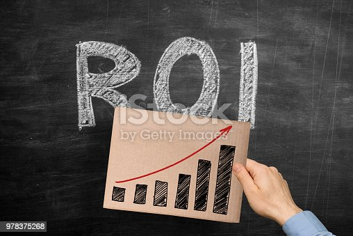 Man holding a hand drawn success graph chart on a cardboard over the word ROI (Return on Investment) written with chalk on blackboard