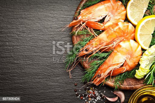 Top view of three king prawns on a wooden plate with some cooking and seasoning ingredients like salt, pepper, olive oil, garlic, lime, and rosemary at the right side of a dark slate background leaving a useful copy space at the center-left of the frame. DSRL studio photo taken with Canon EOS 5D Mk II and Canon EF 100mm f/2.8L Macro IS USM